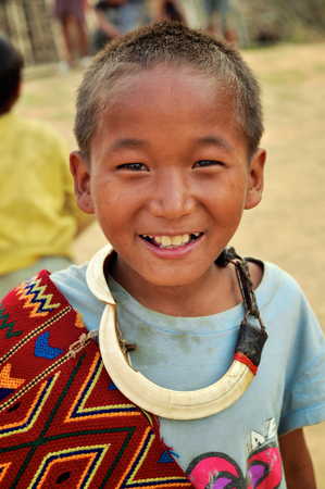 Aoleang, Nagaland, India - April 2012:  Native boy dressed as warrior smiling at camera during Aoleang festival in Aoleang, Nagaland, India. Documentary editorial.