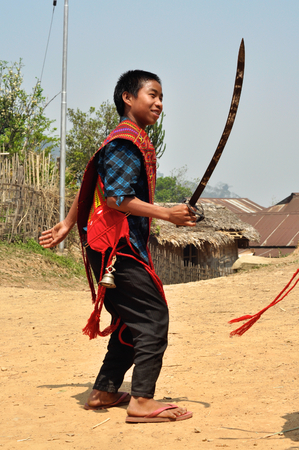 Aoleang, Nagaland, India - April 2012: Native boy with long sword in traditional warrior costume during Aoleang festival in Aoleang, Nagaland, India. Documentary editorial.