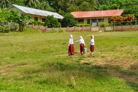 headcloth: Katupat, Indonesia - June 2015: Three young girls in white shirts and red skirts walk home through field in Katupat, Sulawesi, Indonesia. Documentary editorial.