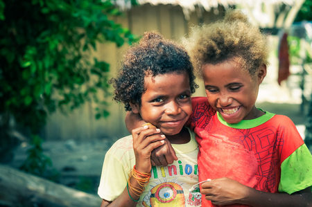 Yenbuba village, Indonesia - June 2015: Two native girls dressed in colourful clothes smile happily and hug at Yenbuba village at Mansuar Island, Raja Ampat, West Papua, Indonesia. Documentary editorial.