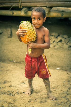 red shorts: Will-will, Papua New Guinea - July 2015: Young half-naked boy in red shorts holds big pineapple in his hands and looks to photocamera in Will-will, Nuku, Papua New Guinea. Documentary editorial.