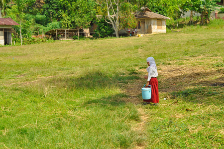 headcloth: Katupat, Indonesia - June 2015: Young girl in white shirt and red skirt carries blue bucket and walks in grass in Katupat, Sulawesi, Indonesia. Documentary editorial.