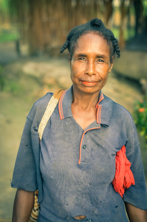 modesty: Avatip, Papua New Guinea - July 2015: Woman in blue t-shirt with bag on her arm smiles and looks to photocamera in Avatip, Sepik river, Papua New Guinea. Documentary editorial. Editorial