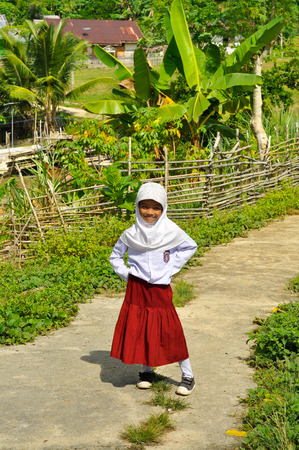 headcloth: Katupat, Indonesia - June 2015: Young girl in white headcloth, shirt and red skirt smiles and poses to photocamera in Katupat, Sulawesi, Indonesia. Documentary editorial. Editorial