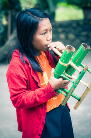 indonesia girl: Suaya, Indonesia - May 2015: Young black-haired girl dressed in orange t-shirt and red sweatshirt plays specific type of bamboo flute in Suaya, in the south-east of Tana Toraja, Sulawesi, Indonesia. Documentary editorial. Editorial