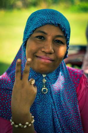 headcloth: Wakai, Indonesia - June 2015: Native woman with blue headcloth and pink shirt smiles to photocamera and holds her hand in symbol of peace in Wakai, Raja Ampat Islands, West Papua, Indonesia. Documentary editorial.