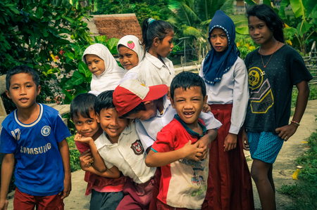 headcloth: Katupat, Indonesia - June 2015: Native girls and boys stand in row and pose to photocamera in Katupat, Sulawesi, Indonesia. Documentary editorial.