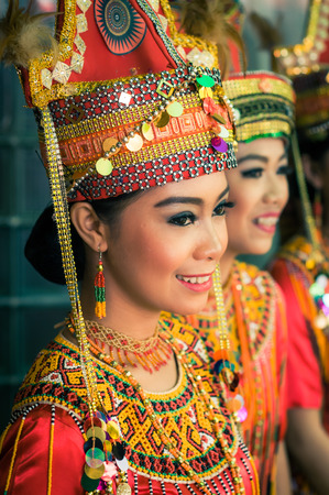 toraja: Makale, Indonesia - May 2015: Photo of pretty young girl in complex red and yellow costume with jewellery made of beads and large hat smiling during wedding in Makale, capital city of Tana Toraja Regency, South Sulawesi, Indonesia. Documentary editorial. Editorial