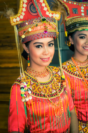 Makale, Indonesia - May 2015: Photo of beautiful young girls dressed in traditional colourful costumes and large hats smiling to photocamera during wedding in Makale, capital city of Tana Toraja Regency, South Sulawesi, Indonesia. Documentary editorial. Editorial
