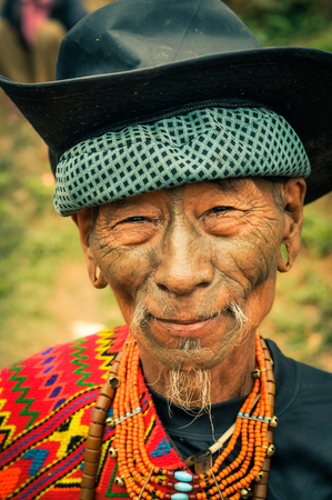 nagaland: Mon, Nagaland - April 2012: Old native man with colourful necklace made of beads and black hat  smiles to photocamera at Aoleang festival in Mon, Nagaland. Documentary editorial.