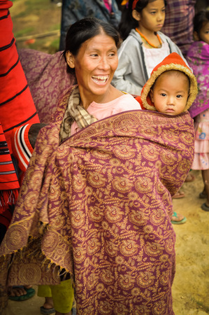 nagaland: Wanching, Nagaland - April 2012: Smiling native woman with beautiful ornamented scarf carries her child on her back during Aoleang festival in Wanching, Nagaland. Documentary editorial. Editorial