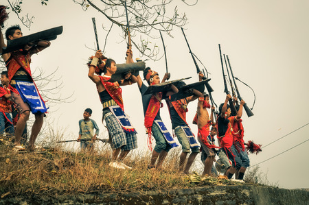 nagaland: Wanching, Nagaland - April 2012: Native boys in traditional costumes with protective shields hold rifles during Aoleang festival in Wanching, Nagaland. Aoleang is main festival of Konyaks from northern Nagaland with indigenous dances, songs and games. Doc Editorial