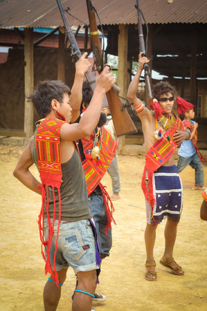 Wanching, Nagaland - April 2012: Photo of three young boys in traditional costumes holding rifles during Aoleang festival in Wanching, Nagaland. Aoleang is festival with indigenous dances, songs and games. Documentary editorial.