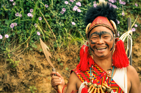 Mon, Nagaland - April 2012: Young native man with black colour on his face poses in traditional costume and hat with fur holding axe and smiling joyfully at Aoleang festival in Mon, Nagaland. Documentary editorial.