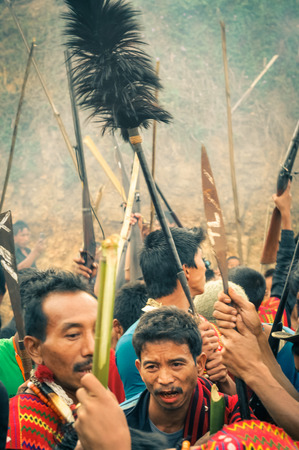 Wanching, Nagaland - April 2012: Crowd of native people holding wooden sticks and rifles at Aoleang festival in Wanching, Nagaland. Documentary editorial.