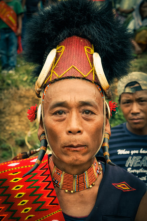 documentary: Mon, Nagaland - April 2012: Native man in traditional colourful costume with necklace made of beads and large hat with fur poses at Aoleang festival in Mon, Nagaland. Documentary editorial. Editorial