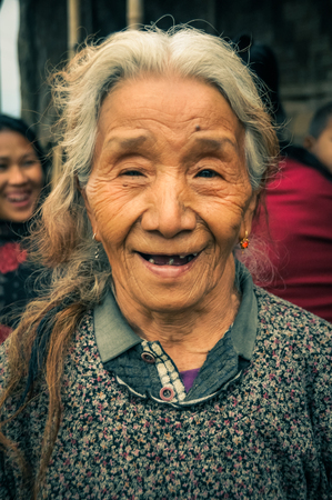 Wanching, Nagaland - April 2012: Old native woman with grey and brown hair smiles to photocamera at traditional Aoleang festival in Wanching, Nagaland. Documentary editorial. Editorial