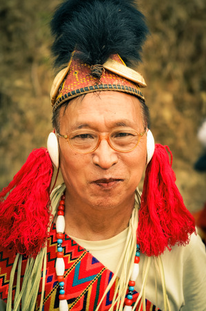 Mon, Nagaland - April 2012: Native man dressed in traditional costume and hat with fur wears glasses and smiles to photocamera at Aoleang festival in Mon, Nagaland. Documentary editorial.
