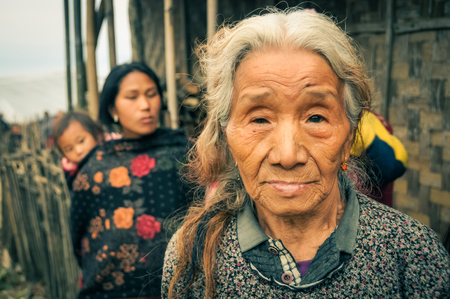 documentary: Wanching, Nagaland - April 2012: Old woman with grey and brown hair looks to photocamera at traditional Aoleang festival in Wanching, Nagaland. Documentary editorial.