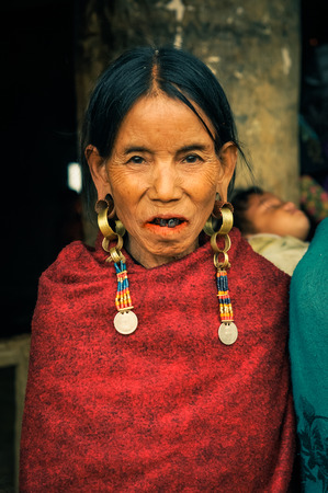nagaland: Wanching, Nagaland - April 2012: Native woman with red scarf and large earrings looks to photocamera during Aoleang festival in Wanching, Nagaland. Documentary editorial.