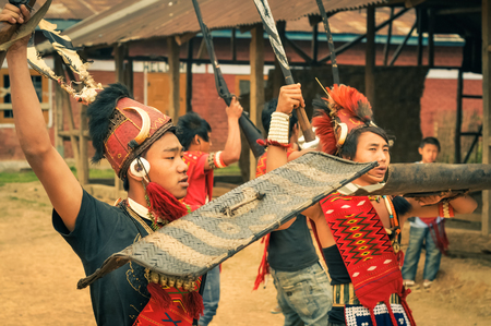 documentary: Wanching, Nagaland - April 2012: Young boys in traditional costumes hold rifles and protective shields during performance at Aoleang festival in Wanching, Nagaland. Aoleang is festival with indigenous dances, songs and games. Documentary editorial.