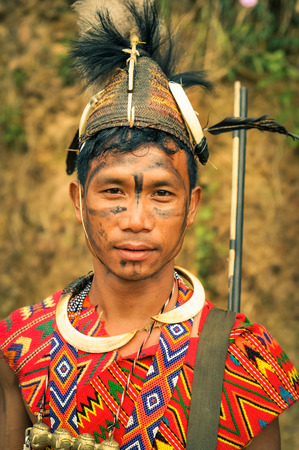 nagaland: Mon, Nagaland - April 2012: Photo of young man dressed in traditional colourful costume and hat at Aoleang festival in Mon, Nagaland. Documentary editorial.