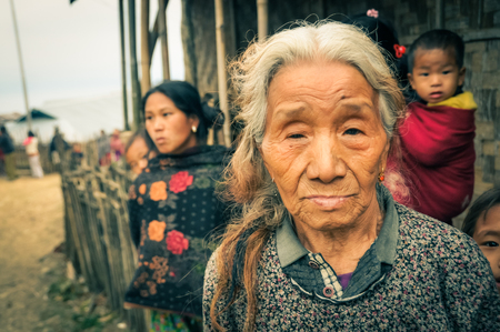 Wanching, Nagaland - April 2012: Old woman with grey and brown hair looks to photocamera at traditional Aoleang festival in Wanching, Nagaland. In background with her house and family. Documentary editorial.