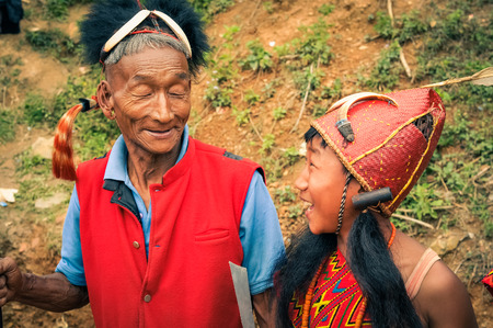 nagaland: Mon, Nagaland - April 2012: Older native man in red vest and with hat made of fur and feather at top poses with young boy in traditional costume at Aoleang festival in Mon, Nagaland. Documentary editorial. Editorial