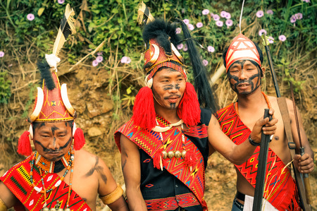 documentary: Mon, Nagaland - April 2012: Native men with black colour on their faces hold rifles and pose in traditional costumes and hats with fur at Aoleang festival in Mon, Nagaland. Documentary editorial.