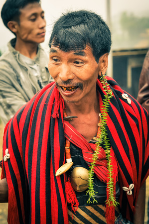 documentary: Wanching, Nagaland - April 2012: Native man in black and red scarf talks and looks to left at Aoleang festival in Wanching, Nagaland. Documentary editorial.