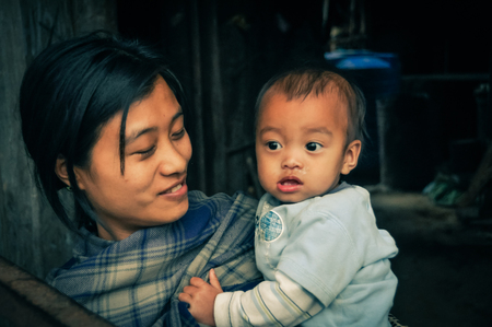 nagaland: Wanching, Nagaland - April 2012: Smiling young mother poses with her beautiful small child at traditional Aoleang festival in Wanching, Nagaland. Documentary editorial.