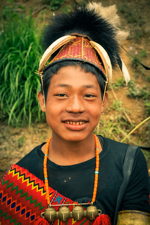 Mon, Nagaland - April 2012: Young native boy with necklace made of beads and large hat with fur smiles to photocamera at Aoleang festival in Mon, Nagaland. Documentary editorial.