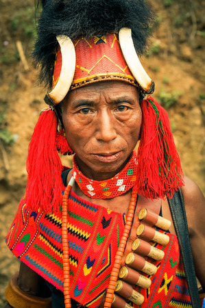 nagaland: Mon, Nagaland - April 2012: Older native man with large red hat with fur and bones dressed in traditional colourful costume looks to photocamera at Aoleang festival in Mon, Nagaland. Aoleang is main festival of Konyaks from northern Nagaland with indigeno