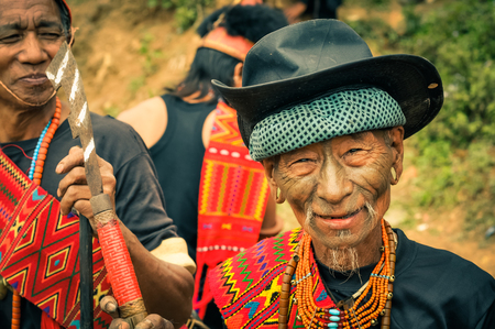 documentary: Mon, Nagaland - April 2012: Old native man with colourful necklace made of beads and black hat  smiles and poses with other people in costumes to photocamera at Aoleang festival in Mon, Nagaland. Documentary editorial. Editorial