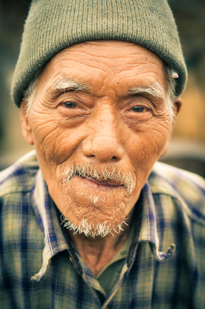nagaland: Wanching, Nagaland - April 2012: Old man with grey moustache and cap on his head looks to photocamera at traditional Aoleang festival in Wanching, Nagaland. Documentary editorial.