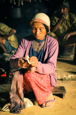 documentary: Wanching, Nagaland - April 2012: Native woman with cap on her head and violet jacket sits on ground and looks down during Aoleang festival in Wanching, Nagaland. Documentary editorial. Editorial