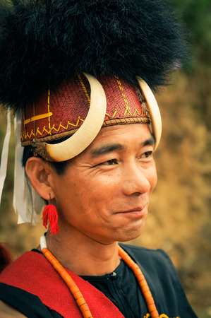 nagaland: Mon, Nagaland - April 2012: Native man with traditional large hat with fur and bones smiles and looks to right at Aoleang festival in Mon, Nagaland. Documentary editorial.