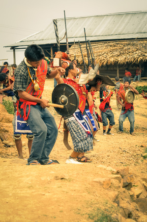nagaland: Wanching, Nagaland - April 2012: Native boys in traditional costumes play hand drums and hold rifles during performance at Aoleang festival in Wanching, Nagaland. Aoleang is festival with indigenous dances, songs and games. Documentary editorial.