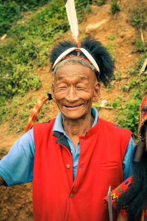 Mon, Nagaland - April 2012: Older native man in red vest and with hat made of fur and feather at top smiles to photocamera at Aoleang festival in Mon, Nagaland. Documentary editorial.