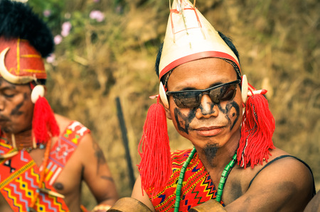 nagaland: Mon, Nagaland - April 2012: Photo of young man dressed in traditional colourful costume and hat wearing sunglasses at Aoleang festival in Mon, Nagaland. Documentary editorial. Editorial
