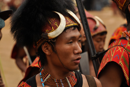 Mon, Nagaland - April 2012: Photo of young native boy in traditional colourful costume and hat made of fur and bones watching performance at Aoleang festival in Mon, Nagaland. Aoleang is biggest and most significant festival of Konyak Nagas of Nagaland. D