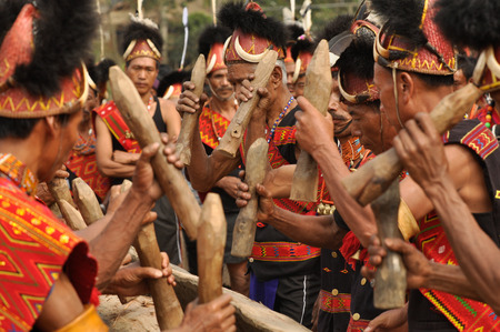 Mon, Nagaland - April 2012: Native men in costumes hold wooden stakes during performance at Aoleang festival in Mon, Nagaland. This festival showcases rich cultural heritage of this country. Documentary editorial.
