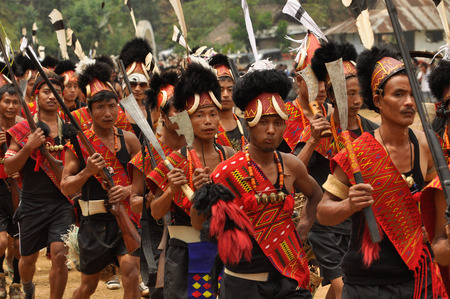 documentary: Mon, Nagaland - April 2012: Photo of native men in traditional costumes and hats with fur and bones holding rifles and marching during performance at Aoleang festival in Mon, Nagaland. Documentary editorial. Editorial