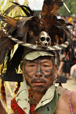 nagaland: Mon, Nagaland - April 2012: Native man with black colour on his face wears hat with black and orange feathers and with small skull and bone in front and looks to photocamera at Aoleang festival in Mon, Nagaland.  Aoleang is biggest and most significant fe Editorial