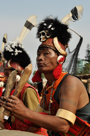 documentary: Mon, Nagaland - April 2012: Photo of native man in costume with hat made of skull and feathers holding wooden stakes during ceremony at Aoleang festival in Mon, Nagaland. This festival showcases rich cultural heritage of this country. Documentary editoria Editorial