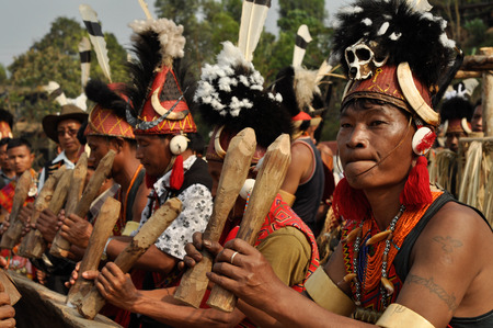 nagaland: Mon, Nagaland - April 2012: Native men in costumes and hats stand in row and hold wooden stakes during performance at traditional Aoleang festival in Mon, Nagaland. This festival showcases rich cultural heritage of this country. Documentary editorial. Editorial