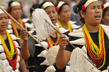 documentary: Mon, Nagaland - April 2012: Native women with large necklaces and headbands dance and sing during performance at Aoleang festival in Mon, Nagaland. Aoleang is biggest and most significant festival of Konyak Nagas of Nagaland. Documentary editorial. Editorial