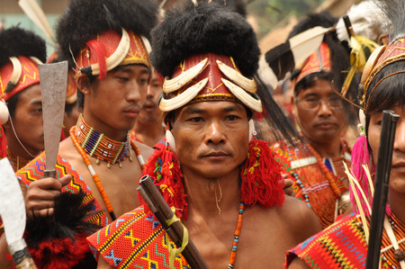 nagaland: Mon, Nagaland - April 2012: Photo of native men in traditional costumes and hats with fur and bones holding rifles during performance at Aoleang festival in Mon, Nagaland.  Aoleang is biggest and most significant festival of Konyak Nagas of Nagaland. Docu