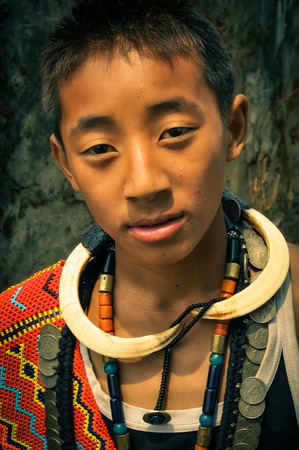 Wanching, Nagaland - April 2012: Young native boy wears traditional necklaces made of beads and other material and looks to photocamera during Aoleang festival in Wanching, Nagaland. Documentary editorial.