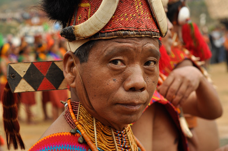 documentary: Mon, Nagaland - April 2012: Native man in traditional costume and hat poses during performance at Aoleang festival in Mon, Nagaland.  Aoleang is biggest and most significant festival of Konyak Nagas of Nagaland. Documentary editorial.